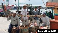 Nelayan mengangkut ikan hasil tangkapan dari kapal ke tempat pelelangan ikan di Lamongan (foto: VOA/Petrus Riski)