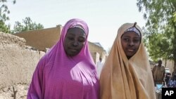 Um das meninas libertadas pelo Boko Haram caminha com a sua mãe, Dapchi, 21 de Março 21, 2018