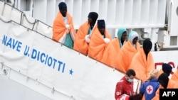 """Des migrants et des réfugiés descendent du bateau de sauvetage """"Diciotti"""" au port de Catania, le 8 janvier 2018."""