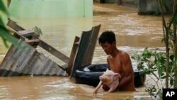 Un residente usa la cámara de una llanta para salvar a un cerdo de las inundaciones causadas por el tifón Koppu en Zaragosa, provincia de Nueva Ecija, al norte de Manila, Filipinas, el lunes, 19 de octubre de 2015.