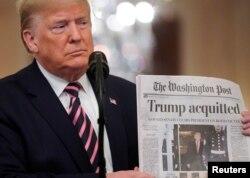 Tổng thống Trump giơ tờ báo The Washington Post với bản tin trang nhất về việc ông được xử trắng án trong phiên xét xử luận tội ở Thượng viện, khi ông phát biểu về sự kiện này trong Phòng Đông của Nhà Trắng ở Washington, ngày 6 tháng 2, 2020.