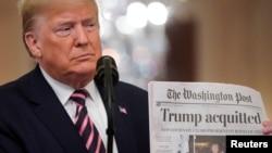 Le président américain Donald Trump brandit une copie de la Une du Washington Post qui annonce qu'il a été acquitté par le Sénat, le 6 février 2020.