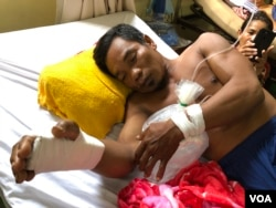 Boeun Bol, 43, with a broken right wrist and bruises on his back, rests on a hospital bed in Phnom Penh, Cambodia, May 11, 2020. (Sun Narin/VOA Khmer)