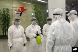 FILE - State Commission of Quality Management staff in protective gear and with disinfectant prepare to check the health of travelers arriving from abroad at the Pyongyang Airport in Pyongyang, North Korea, Feb., 1, 2020.