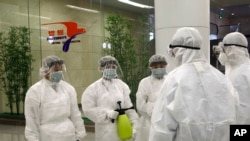 State Commission of Quality Management staff in protective gear and disinfectant prepare to check the health of travelers arriving from abroad at the Pyongyang Airport in Pyongyang, North Korea, Feb., 1, 2020.