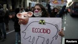 Seorang pedemo menunjukkan poster sambil berpawai ke Istana Kepresidenan Casa Rosada untuk memprotes kesepakatan antara Argentina dan China untuk memproduksi dan mengekspor daging babi ke China, di Buenos Aires, Argentina, Senin, 31 Agustus 2020. (Foto: R
