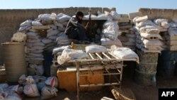 ນັກລົບຈາກກຸ່ມ Free Syrian Army (FSA) ນັ່ງຢູ່ເທິງສິ່ງກີດຂວາງ ໃນຂະນະທີ່ລາວ ປ້ອງກັນທີ່ໝັ້ນແຫ່ງໜຶ່ງ ຢູ່ແນວໜ້າ ໃນເມືອງ Aleppo ທາງພາກເໜືອ ຂອງຊີເຣຍ.