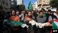 Palestinian mourners carry the bodies of members of the al-Dallu family during a funeral procession in Gaza City on November 19, 2012.