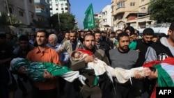 ຊາວປາແລັສໄຕໄວ້ອາໄລແກ່ດວງວິນຍານພວກເສຍຊີວິດ ໂດຍການຫາມສົບຂອງສະມາຊິກຂອງຄອບຄົວ al-Dallu during ໃນພິທີສົ່ງສະການໃນເມືອງ Gaza ໃນວັນທີ 19 ພະຈິກ, 2012.