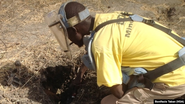 Cons Wani, who works with the Danish Demining Group, brushes dirt away to reveal a rocket-propelled grenade that was found in the center of Bentiu, in South Sudan. (VOA/Bonifacio Taban)