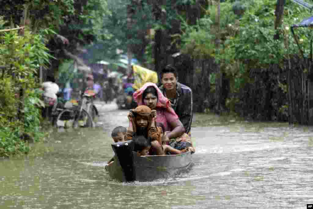 Local residents ride a boat on a road flooded by the Bago River in Bago, 80 kilometers (50 miles) northeast of Yangon, Myanmar.