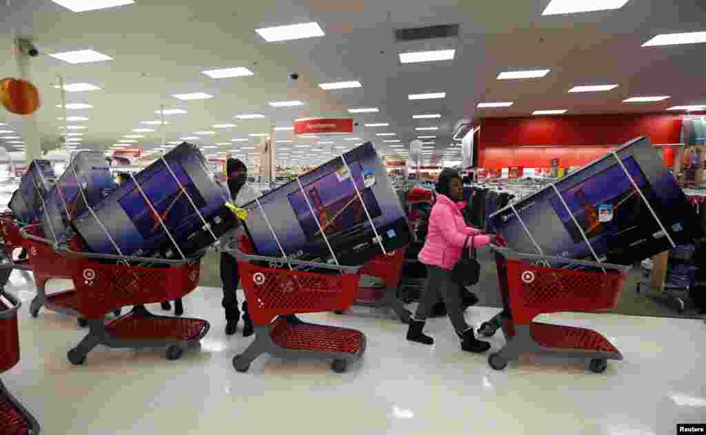 Thanksgiving Day holiday shoppers line up with television sets on discount at the Target retail store in Chicago, Illinois, Nov. 28, 2013.