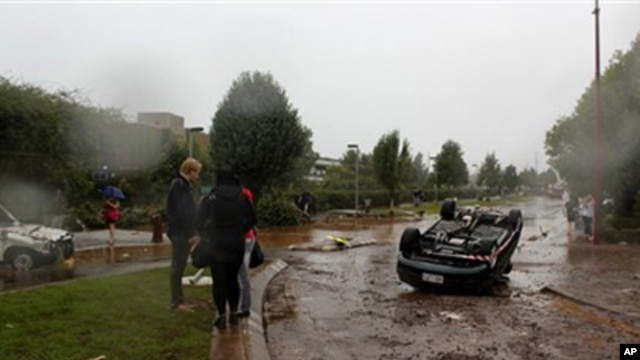People survey the damage after a flash flood tossed vehicles down a street in Toowomba, Australia, 10 Jan 2011