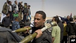 A rebel carries Rocket Propelled Grenades (RPG) after taking Ajdabiya, south of Benghazi, eastern Libya, March 26, 2011