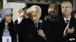Palestinian President Mahmoud Abbas, center, delivers a speech as Palestinian Prime Minister Rami Hamdullah, right, claps during a ceremony to celebrate the 50th anniversary of the start of the Fatah movement, in the West Bank city of Ramallah, Dec. 31, 2014.