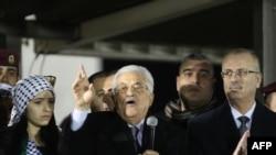 ប្រធានាធិបតីប៉ាឡេស្ទីន Mahmoud Abbas (កណ្តាល) ថ្លែងសន្ទរកថាខណៈពេលដែលលោកនាយករដ្ឋមន្រ្តីប៉ាឡេស្ទីន Rami Hamdullah (ស្តាំ) ទះដៃអប់អរក្នុងពិធីរំឭកខួប៥០ឆ្នាំនៃការបង្កើតចលនា Fatah នៅតបន់ West Bank ក្នុងទីក្រុង Ramallah កាលពីថ្ងៃទី៣១ ខែធ្នូ ឆ្នាំ២០១៤។
