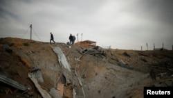 Palestinianos inspeccionam a área afectada pelo ataque israelita neste Sábado, em resposta ao disparo de um rocket a partir de Gaza. Março 18, 2017