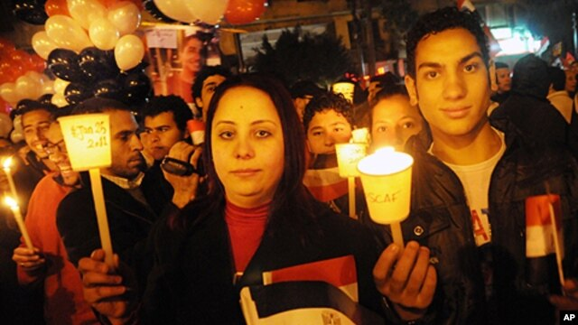 Egyptians hold lit candles during New Year's Eve in Tahrir Square, Cairo, Saturday, Dec. 31, 2011.