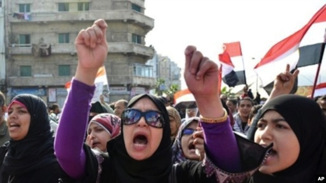 Egyptian protestors wave national flags and shout anti-government slogans during mass rally in the northern Mediterranean port of Alexandria on November 25, 2011.