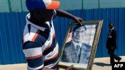 Mmoja wa waombolezaji abeba picha ya marehemu Robert Mugabe, 11 septemba 2019.