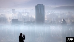 A person takes a picture of the smog over Santiago,