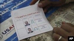 Seorang petugas Pemilu Mesir mempersiapkan surat suara di sebuah TPS di Kairo, Sabtu (16/6).