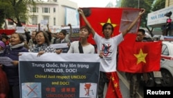 Anti-China protesters hold Vietnamese national flags and anti-China banners while marching on a street in Hanoi, December 9, 2012.