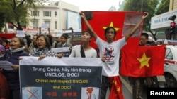Người biểu tình chống Trung Quốc cầm quốc kỳ Việt Nam và các biểu ngữ chống Trung Quốc tuần hành trên đường phố Hà Nội, ngày 9/12/2012.