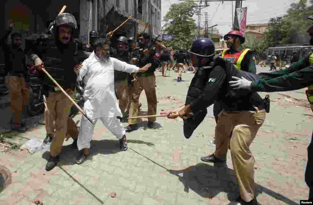 Police beat a supporter of Tahir-ul Qadri of the political party Pakistan Awami Tehreek during a protest in Lahore, Pakistan, June 17, 2014.