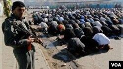 Seorang polisi berjaga saat para jemaah melaksanakan sholat Idul Adha di Kabul (6/11).