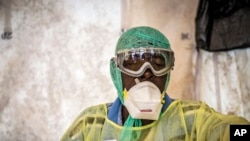 Un agent de santé couvert d'un équipement de protection, examine des patients pour Ebola sous une tente de dépistage, à l'hôpital gouvernemental de Kenema situé dans la province de l'Est à environ 300 km de la capitale de Freetown, Sierra Leone, 11 août 2014