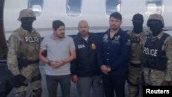 Efrain Antonio Campo Flores (segundo desde la izquierda) y Franqui Fancisco Flores de Freitas (tercero desde la derecha), aparecen junto a agentes de la ley, tras ser arrestados en Puerto Príncipe, Haití, en noviembre de 2015.