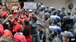 Protesters of the Economic Freedom Fighters confront riot police near parliament in Cape Town, South Africa, Thursday, Feb. 12, 2015.