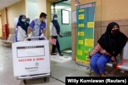 Seorang petugas menarik sebuah kotak berisi vaksin virus corona (COVID-19) di sebuah puskesmas untuk program vaksinasi massal, di Jakarta, 13 Januari 2021. (Foto: Willy Kurniawan/Reuters)