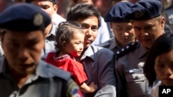 Reuters journalist Kyaw Soe Oo carries his daughter as he is escorted by Myanmar police to trial after a break, Feb. 1, 2018, outside of Yangon, Myanmar. A lawyer for the two Reuters journalists Wa Lone and Kyaw Soe Oo, charged with illegally handling government secrets, says a court had denied their request to be released on bail.