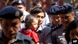 Reuters journalist Kyaw Soe Oo carrying his daughter is escorted by Myanmar police as he re-enter to the trial after a break Feb. 1, 2018, outside of Yangon, Myanmar.