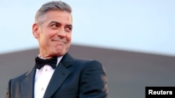 "U.S. actor George Clooney smiles as he arrives on the red carpet for the premiere of ""Gravity"" at the 70th Venice Film Festival in Venice, August 28, 2013."