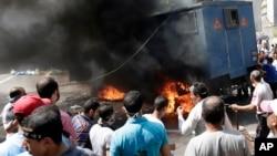 在警民冲突中穆尔西支持者包围一辆燃烧的警车