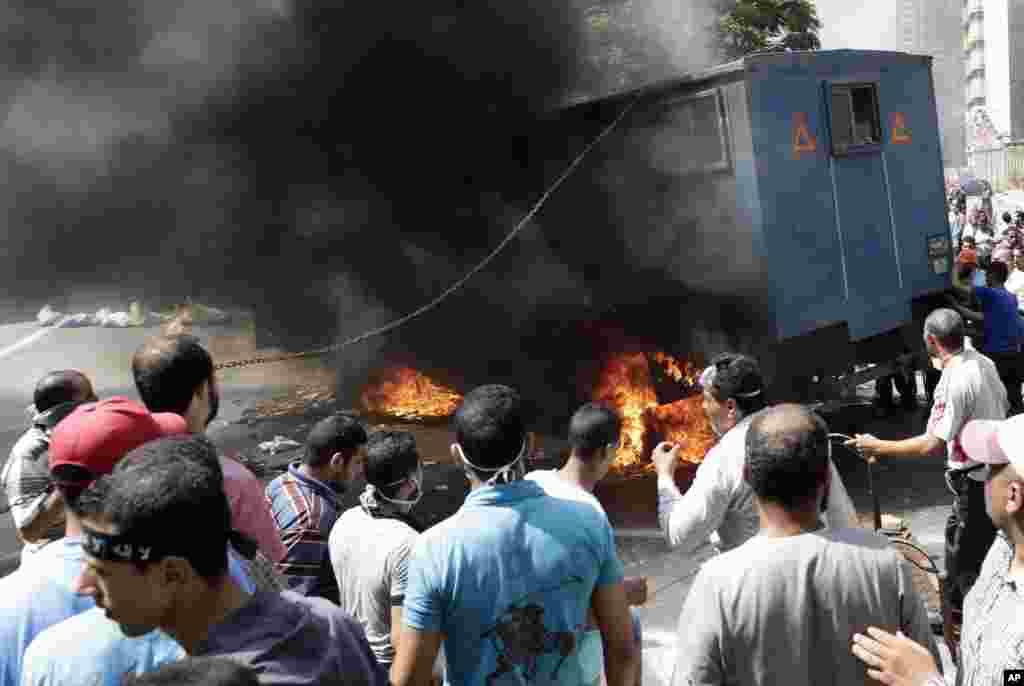 Manifestantes pro-Morsi observam um carro da polícia queimar durante confrontos com as forças de segurança egípcias no bairro Mohandessin em Cairo.