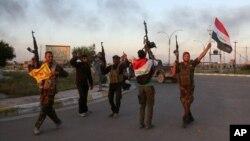Pasukan Irak dan milisi Syiah merayakan kemenangan setelah merebut kota Tikrit, 130 kilometer di sebelah utara Baghdad, Selasa (31/3).