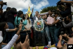 Venezuela's self-declared interim leader Juan Guaido speaks to supporters during a gathering to propose amnesty laws for police and military, at a public plaza in Las Mercedes neighborhood of Caracas, Venezuela, Saturday, Jan. 26, 2019. (AP Photo)