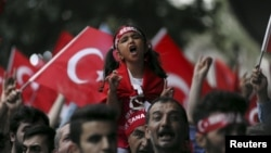 On the same day as a PKK bombing in Igdir province, supporters of ultranationalist groups march with Turkish national flags during a protest against Kurdish militant attacks on Turkish security forces, in Istanbul, Sept. 8, 2015.