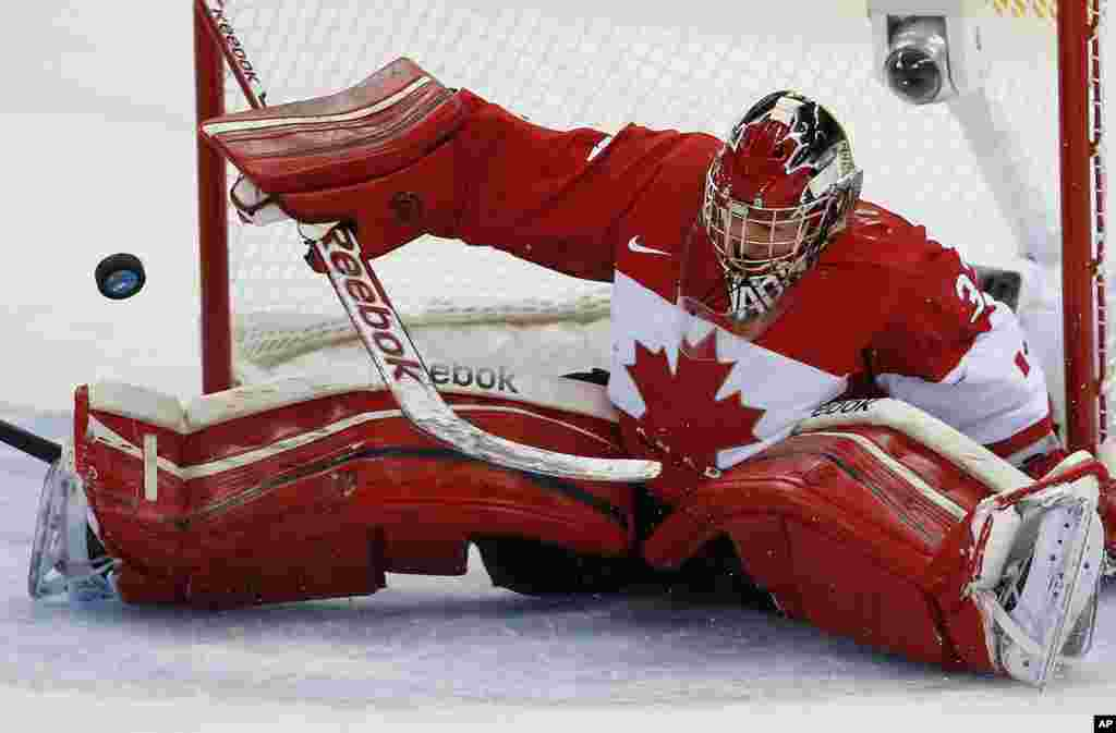Goalkeeper Charline Labonte of Canada bats the puck away during the women's ice hockey game against the United States at Shayba Arena, Sochi, Russia, Feb. 12, 2014.