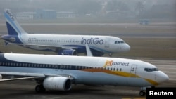 An IndiGo Airlines aircraft and JetKonnect Boeing 737 aircraft taxi at Mumbai's Chhatrapathi Shivaji International Airport on February 3, 2013.