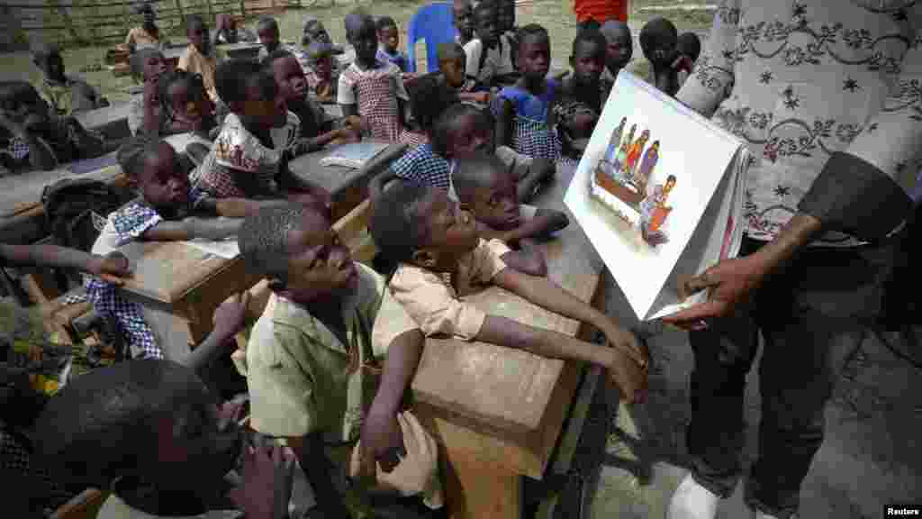 A man shows a picture to students during a United Nations Children's Fund (UNICEF) Ebola awareness drive in Gueupleu, Man, western Ivory Coast, Nov. 3, 2014.