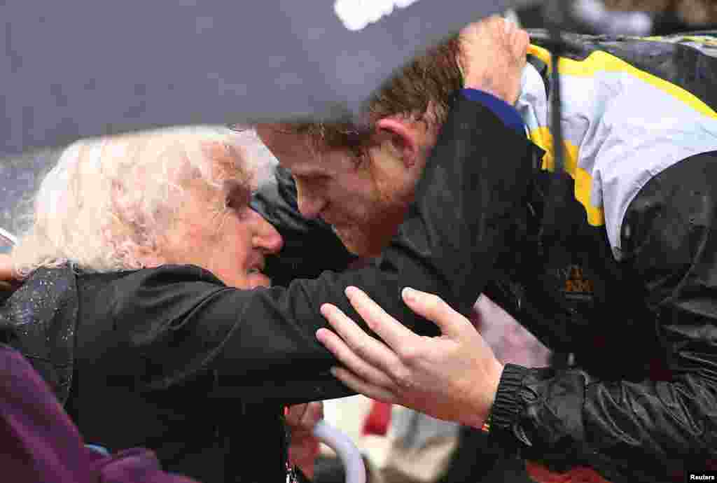 Britain's Prince Harry hugs Daphne Dunne, 97, during a walk around The Rocks district in rainy Sydney, Australia, during his promotion of the 2018 Invictus Games.