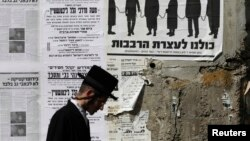 An ultra-Orthodox Jewish man walks past a street poster in Jerusalem's Mea Shearim neighborhood, inviting the public to a protest against government plans to draw more ultra-Orthodox men into the conscript army, June 3, 2013.