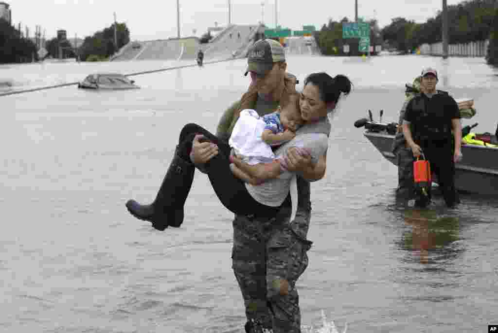 Houston Police SWAT officer Daryl Hudeck carries Catherine Pham and her 13-month-old son Aiden after rescuing them from their home surrounded by floodwaters from Tropical Storm Harvey, Aug. 27, 2017, in Houston.