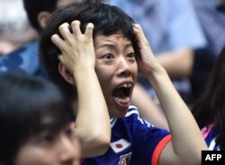 TOPSHOTSA Japanese football supporter reacts as she attends a public screening in Tokyo on July 6, 2015, of the 2015 FIFA Women's World Cup final between Japan and USA being played in Vancouver, British Columbia. AFP PHOTO / KAZUHIRO NOGI