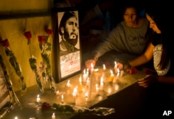 Students place candles around an image of the late Cuban leader Fidel Castro, at the university where Castro studied law as a young man, during a vigil in Havana, Cuba, Nov. 26, 2016.